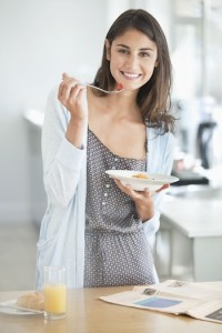 Portrait of smiling woman eating breakfast and reading newspaper